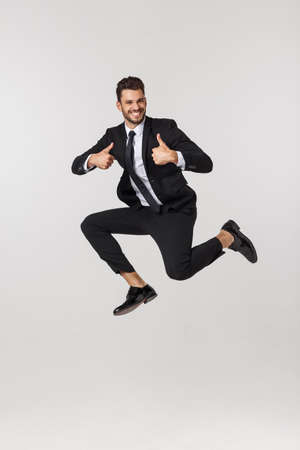 Portrait of a happy businessman jumping in air against isolated white background.