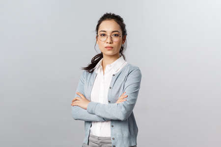 Serious-looking determined attractive asian woman, tutor or teacher starting online lesson with class standing self-assured with normal focused expression, cross arms on chest