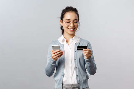 Technology, online and mobile lifestyle concept. Cheerful relaxed asian housewife, employee working from home, order food and groceries with smartphone app, use credit card and phone