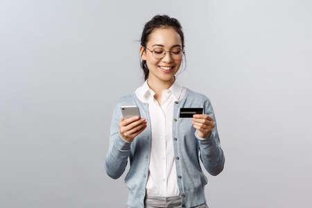 技术,网上和移动生活方式概念。快乐轻松的亚洲主妇,员工在家里工作,订购食品和杂货与智能手机应用,使用信用卡和手机