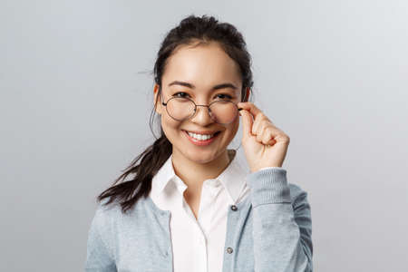 Advertisement, people and emotion concept. Close-up portrait of confident, professional asian brunette female, take-off glasses and look pleased camera, express satisfaction and self-assurance 版權商用圖片