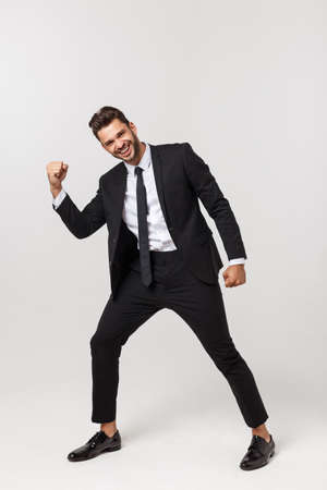 Cheerful young bearded business man show hand up excited with clenched fists. Full length portrait business man isolated over white studio background