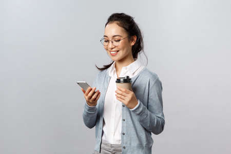 Office lifestyle, business and people concept. Attractive young korean woman checking her phone messages, drinking take-away coffee, look at smartphone display with pleased smile, texting in chat 版權商用圖片