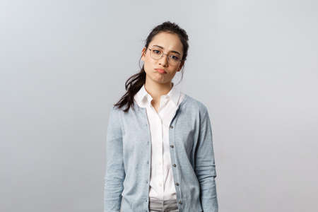 Portrait of sighing displeased and gloomy young asian girl in glasses, pouting and looking disappointed camera, express regret or feel uneasy over failure at work, grey background Stock Photo