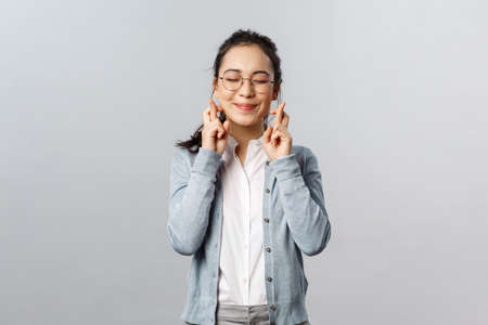 Emotions, people and lifestyle concept. Hopeful, dreamy good-looking asian girl close eyes and smiling daydreaming, having faith wish come true, cross fingers good luck, praying over grey background