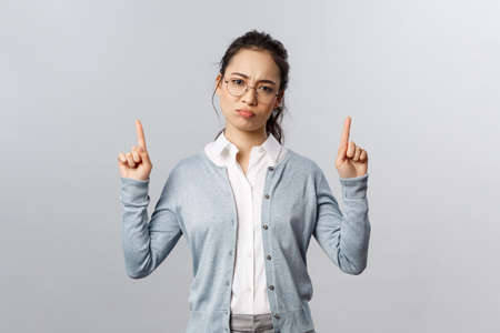 Skeptical, disappointed cute asian girl dont recommend this product, pointing fingers up with bothered, complaining and gloomy expression, have negative thoughts about company, grey background 版權商用圖片