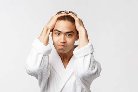 Beauty, spa and leisure concept. Portrait of sick and tired, tensed angry asian man holding hands on head, biting lip and frowning, feel stress, standing frustrated and bothered, white background