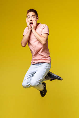 Summer vacation, education and lifestyle concept. Vertical shot of shocked and amazed, gasping asian man heard overwhelming news, touch face and jumping surprised, stand yellow background