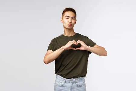 People, emotions and lifestyle concept. Cute and silly male student, asian guy wink cheeky and flirty, pouting or folding lips for kiss and showing heart over chest, express sympathy and love