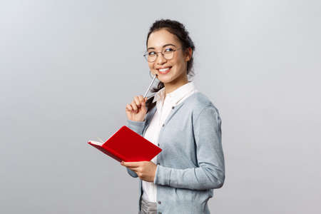 Teaching, education and university lifestyle concept. Creative talented young asian woman turn back and smiling thoughtful, have interesting idea, reading siblings diary, hold planner