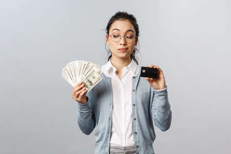 Business, finance and investment concept. Thoughtful indecisive cute asian girl look tempting at cash dollars, holding money and credit card, shopping, think where invest, grey background Banque d'images - 144133431