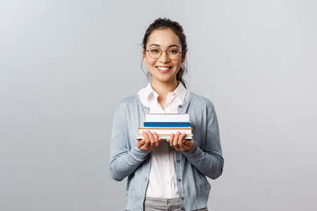 Education, teachers, university and schools concept. Smart and enthusiastic asian female student studying for exams, carry piles of books to prepare homework for classes, smiling happy