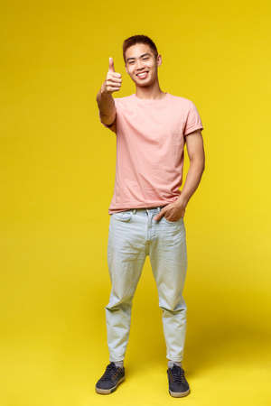 Lifestyle, education and people concept. Vertical portrait of stylish asian hipster guy, show thumb-up and smiling pleased, recommend product, approve and guarantee great quality, yellow background