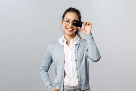 Technology, online purchases and finance concept. Good-looking, lovely asian woman in glasses, showing credit card over eye and smiling, recommend pay internet with bank account Banque d'images - 144134648