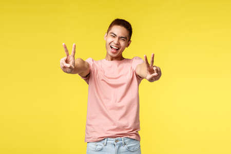 Lifestyle, travel and people concept. Cheerful, enthusiastic handsome asian man smiling and squinting happily, showing peace signs, enjoying summer vacation, standing yellow background