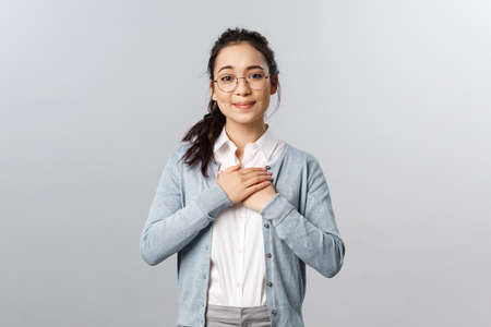Portrait of touched, heartwarming lovely asian woman in glasses, listening to her students complimenting her class, hold hands on heart sighing, look at something adorable and sweet, smiling tender