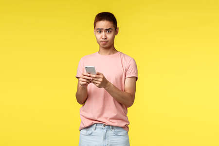 Technology, communication and lifestyle concept. Portrait of alarmed asian guy in pink t-shirt, using mobile phone text alarmed at bad news he read internet, standing bothered and frustrated