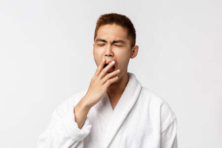 Beauty, spa and leisure concept. Portrait of young asian sleepy man, yawning and cover mouth with closed eyes, wearing bathrobe, waking up in hotel during vacation, white background Foto de archivo