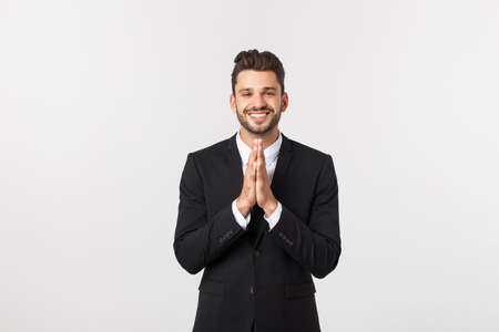 Handsome young business man standing praying, isolated over white background. Concept of idea, ask question, think up, choose, decide