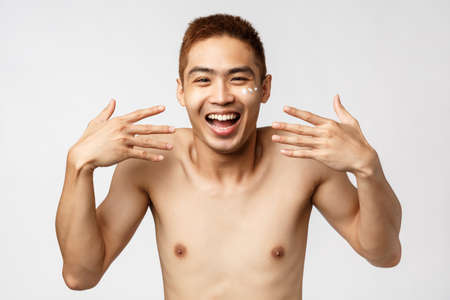 Beauty, people and leisure concept. Close-up portrait of enthusiastic, amused asian handsome man with bare torso, shaking hands and laughing, smiling upbeat, apply facial cream