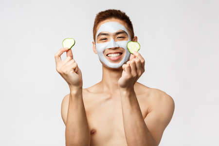 Beauty, skincare and spa concept. Happy handsome asian man with naked torso, taking care of skin, self-distancing enjoying and relaxing leisure, apply face mask and put cucumber on eyes