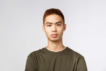 Close-up portrait of serious-looking japanese guy in green t-shirt, look serious and determined, listen to tutor during online lecture while social-distancing at home, standing grey background