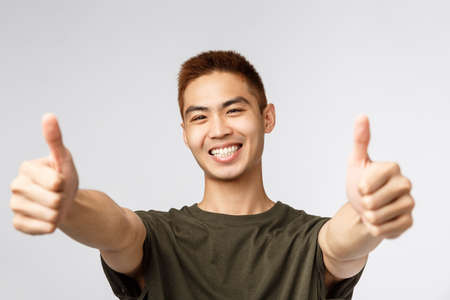People, different expressions and lifestyle concept. Close-up portrait of enthusiastic japanese guy saying yes, approve product, give recommendation and guarantee best quality, thumbs-up