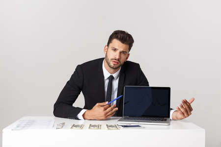 businessman sitting at desk point finger at isolated white laptop screen with empty copy space, handsome young business man