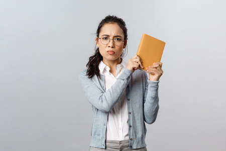 Education, teachers, university and schools concept. Angry displeased, pouting asian girl raise planner want to bit someone with book as hear rude joke, frowning and sulking displeased, threatening Stock Photo