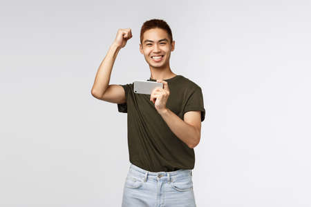 Technology, online lifestyle and communication concept. Portrait of rejoicing, happy asian man raising hand up in yes, hooray emotion, winning, hold mobile phone, pass level in smartphone game Stok Fotoğraf