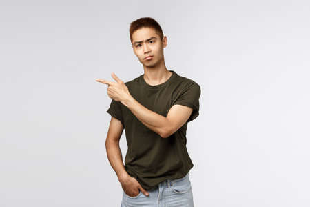 Portrait of skeptical, gloomy young asian male student hate self-distancing from friends and college pals, pointing finger left and grimacing camera, pouting upset, feel envy or regret Archivio Fotografico