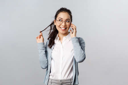 Office lifestyle, business and people concept. Talkative cute and silly female meployee, asian girl roll strand of hair on finger, look away dreamy and smiling, talking on phone gossiping