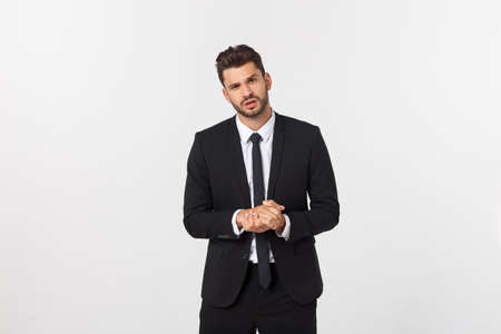 Well dressed man in the studio emphasize thoughtful thinking, think carefully and try to choose to hold hands and stand against the white background.