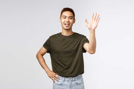 People, emotions and lifestyle concept. Portrait of friendly cheerful asian man saying hi, welcome person as waving hand, informal greeting, hello nice to meet you, standing grey background