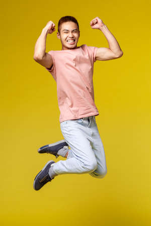 Summer vacation, education and lifestyle concept. Vertical shot of happy athletic asian guy, flex biceps and smiling upbeat, jumping from joy, triumphing, celebrating victory, yellow background