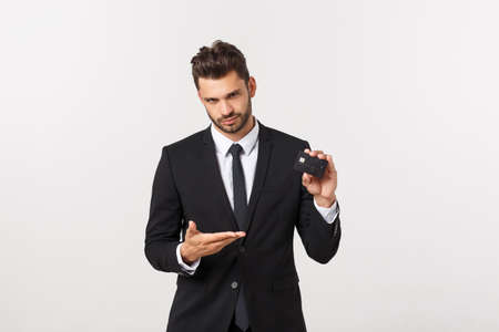 Surprised, speechless and impressed handsome caucasian businessman in classic suit showing credit card, say wow, standing white background astonished
