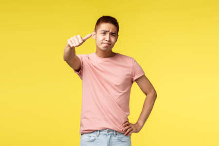 Portrait of skeptical displeased asian man in pink t-shirt, judging, express own opinion to bad thing, rate product is average, thumb-down and grimacing disappointed, yellow background 免版税图像