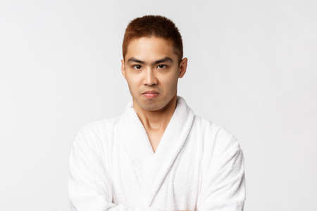 Beauty, spa and leisure concept. Portrait of grimacing, angry and offended asian man sulking, frowning upset, cross arms chest displeased, standing white background disappointed