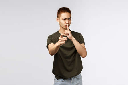 You better keep mouth shut. Portrait of angry serious-looking asian man pointing at camera and shushing scolding you for being noisy and loud, tell person be quiet and dont speek, grey background Stockfoto