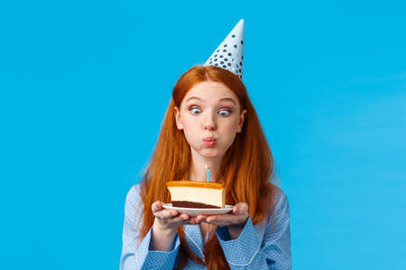 Silly and cute glamour redhead caucasian female in b-day cap and nightwear, holding slice cake with candle, blowing out and making wish with funny expression, standing blue background