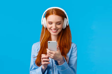 Technology addication, lifestyle and women concept. Cheerful good-looking redhead woman in nightwear, wearing big headphones listen music, smiling pick songs in smartphone app Фото со стока