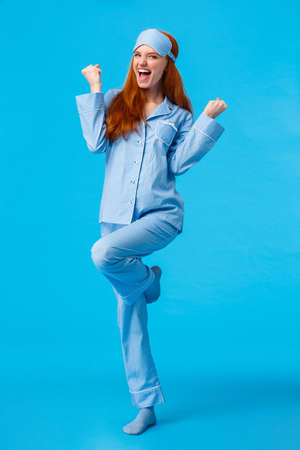 Win, luck and happiness concept. Cheerful caucasian redhead female in nightwear and sleep mask feeling like champion, celebrating victory, triumphing, fist pump say yes and raise leg Фото со стока