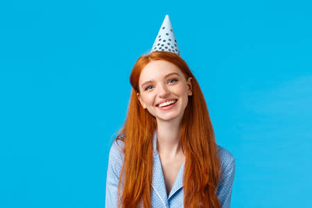 Happiness, beauty and celebration concept. Cheerful carefree redhead woman in b-day hat and nightwear, smiling joyfully, have sleepover birthday party, standing blue background