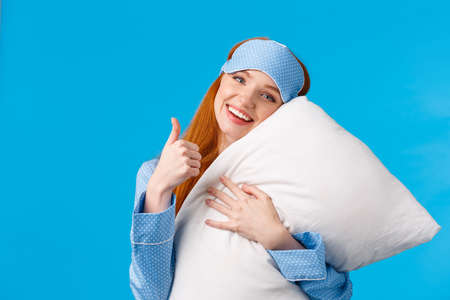 Saying yes to good healthy sleep. Cheerful pretty redhead woman in sleep mask and nightwear, hugging soft pillow showing thumbs-up in approval, like gesture, standing pleased blue background Фото со стока