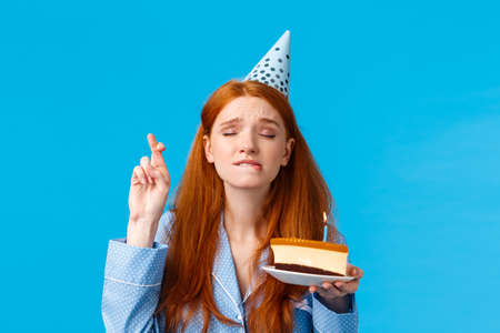 Eager and hopeful redhead european girl in nightwear, close eyes and cross fingers good luck, biting lip tempting or exciting, making wish hold birthday cake with lit candle, wear b-day cap Фото со стока