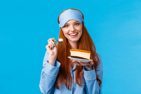 Glamour attractive redhead caucasian female in nightweat, sleep mask eating delicious cake, holding tasty dessert and spoon, smiling having cheat day, wearing sleep mask and pyjama