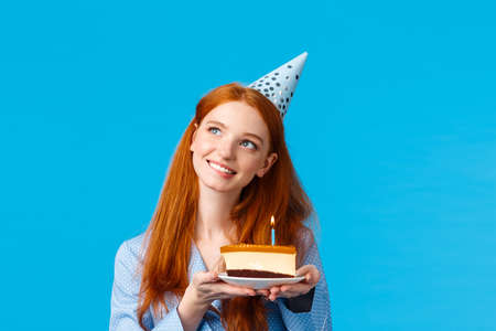 Dreamy, tender and feminine redhead caucasian girl thinking looking up thoughtful with tempting smile holding b-day cake pondering what wish make as blowing candle, celebrating birthday