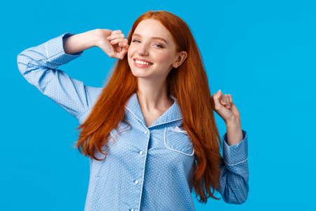 Tender sleepy redhead teenage girl stretching with hands raised, smiling satisfied, had great sleep, waking up and grinning delighted, waiting for morning coffee, wearing pyjama, blue background