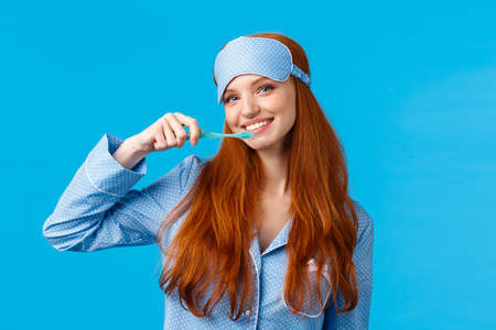 Cheerful cute redhead woman in nightwear, pyjama and sleep mask, brushing teeth holding toothbrush and smiling cheerful, wake up and taking care hygiene, standing blue background