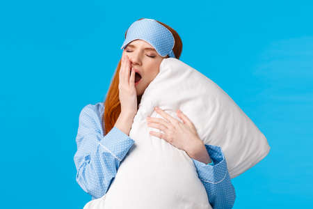 Feminine and glamour lovely redhead teenager yawning and cover opened mouth, feeling sleepy and tired got to bed, hugging pillow, close eyes having good night, standing blue background